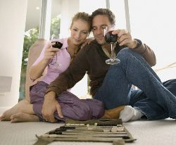 adults playing board game and sipping wine. Ideas for a fun date.
