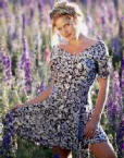 sexy woman in pretty dress posing in field of flowers