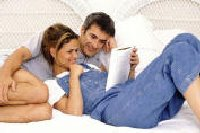 couple laughing and reading relationship compatibility test in bed