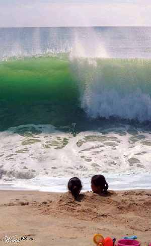 two people buried in sand up to their necks and large wave about to hit them