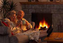 older couple cuddling by fireplace