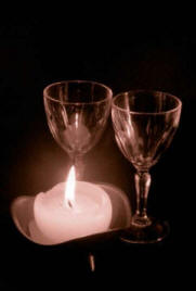 2 wine glasses illuminated by flickering romantic candle