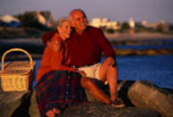 older couple at the seashore snuggling with picnic basket