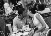 couple in restaurant in romantic kiss after dinner