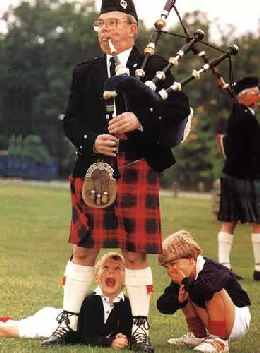 scotsman playing bagpipes with laughing children