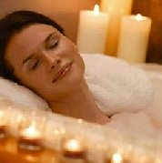 smiling woman in bathtub with candles
